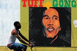 (FILES) In this file photo taken on February 8, 2009 a man pedals past a mural of late musician Bob Marley in Kingston. - Reggae music, whose chill, lilting grooves won international fame thanks to artists like Bob Marley, on November 29, 2018 secured a coveted spot on the United Nations' list of global cultural treasures. (Photo by Jewel SAMAD / AFP)